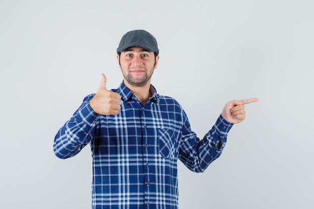 Młody człowiek pokazując kciuk w górę, wskazując na bok w koszuli, czapce i wyglądający wesoło. przedni widok.