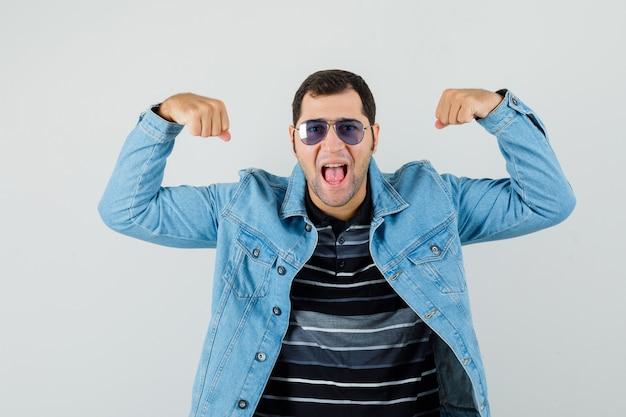 Młody człowiek pokazując mięśnie ramion w t-shirt, kurtkę i wyglądający energicznie. przedni widok.