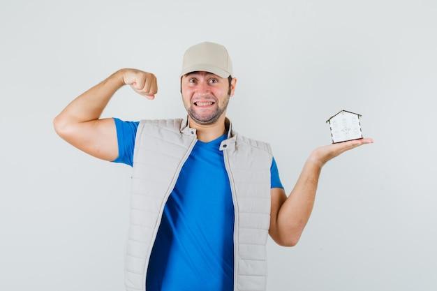 Młody człowiek pokazując mięśnie, trzymając model domu w t-shirt, kurtkę, czapkę i patrząc na szczęście, widok z przodu.