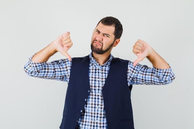 Młody człowiek pokazując podwójne kciuki w dół w koszuli, kamizelce i patrząc zdenerwowany.
