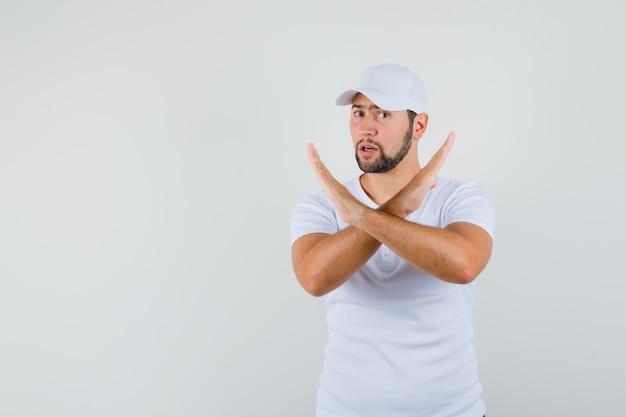 Młody człowiek pokazując zamknięty gest w białą koszulkę, czapkę i patrząc poważny, przedni widok. miejsce na tekst