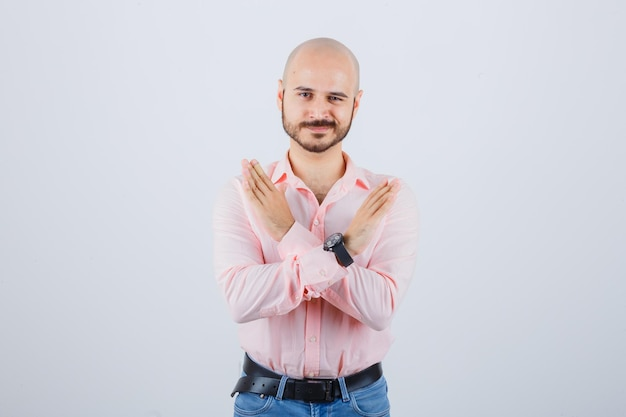 Młody człowiek pokazując zamknięty gest w różowej koszuli, dżinsach, widok z przodu.