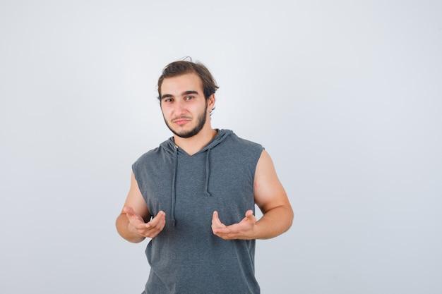 Młody człowiek pokazujący bezradny gest w bluzie bez rękawów i wyglądający na zdziwionego. przedni widok.