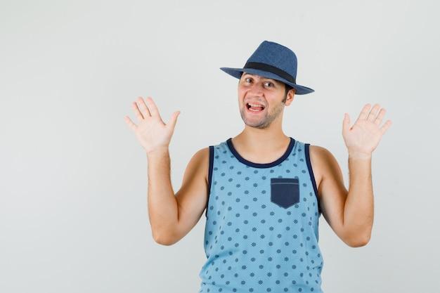 Młody człowiek pokazujący dłonie w geście kapitulacji w niebieskim podkoszulku, kapeluszu i zadowolonym spojrzeniu. przedni widok.