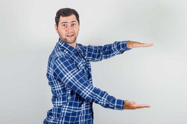 Młody człowiek pokazujący duży znak rozmiaru w kraciastej koszuli