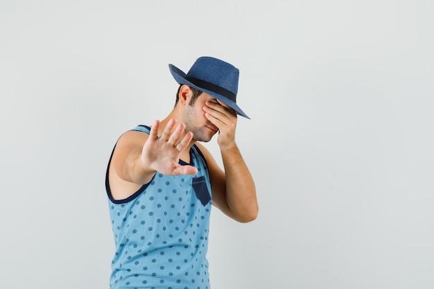 Młody człowiek pokazujący gest odmowy z ręką na oczach w niebieskim podkoszulku, kapeluszu i przestraszony, widok z przodu.