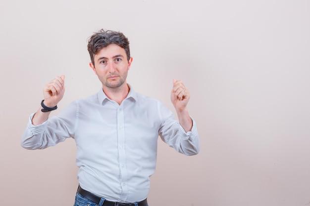 Młody człowiek pokazujący gest pieniędzy w białej koszuli i dżinsach