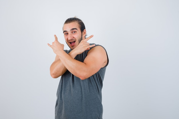 Młody człowiek pokazujący gest rocka w bluzie bez rękawów i wyglądający na szczęśliwego, widok z przodu.