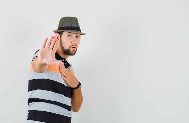 Młody człowiek pokazujący gest stopu, trzymając dłoń na klatce piersiowej w koszulce, kapeluszu i patrząc podekscytowany