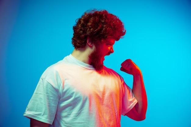Młody człowiek pokazujący muscules i krzyczący