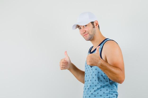 Młody człowiek pokazujący podwójne kciuki do góry w niebieskim podkoszulku, czapce i wyglądający wesoło.