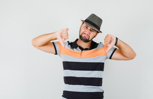 Młody człowiek pokazujący podwójne kciuki w dół w koszulce, kapeluszu i wyglądający na rozczarowanego