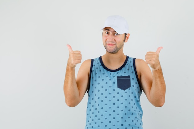 Młody człowiek pokazujący podwójne kciuki w niebieski podkoszulek, czapkę i wyglądający wesoło, widok z przodu.