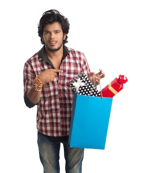 Młody człowiek pokazujący rakhi na dłoni z torbami na zakupy i pudełkiem prezentowym z okazji festiwalu raksha bandhan.