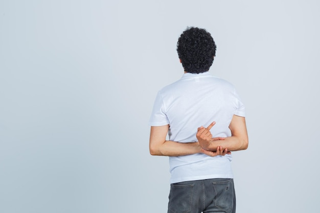 Młody człowiek pokazujący środkowy palec za plecami w białej koszulce, spodniach i patrząc zamyślony, widok z tyłu.