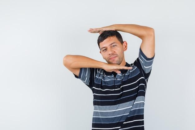 Młody człowiek pokazujący tradycyjny taniec gest w t-shirt i patrząc radosny, widok z przodu.