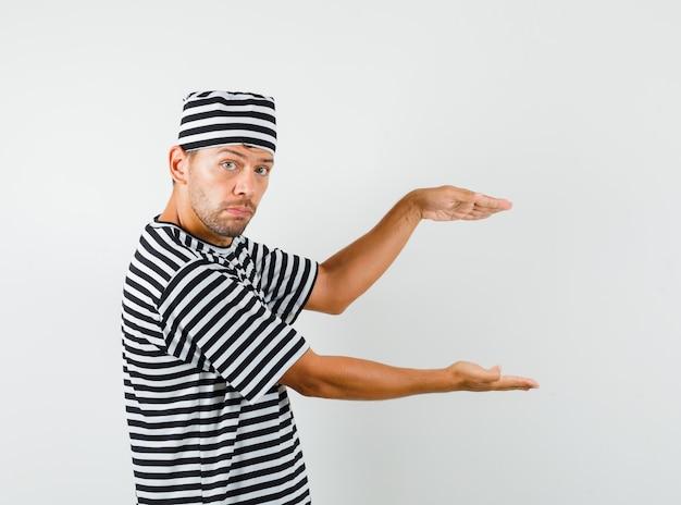 Młody człowiek pokazujący znak rozmiaru w paski t-shirt, kapelusz.