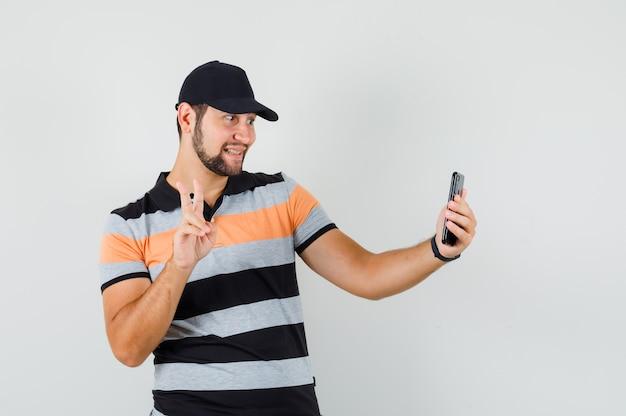 Młody człowiek pokazujący znak v podczas robienia selfie w t-shirt, czapkę i wyglądający wesoło.