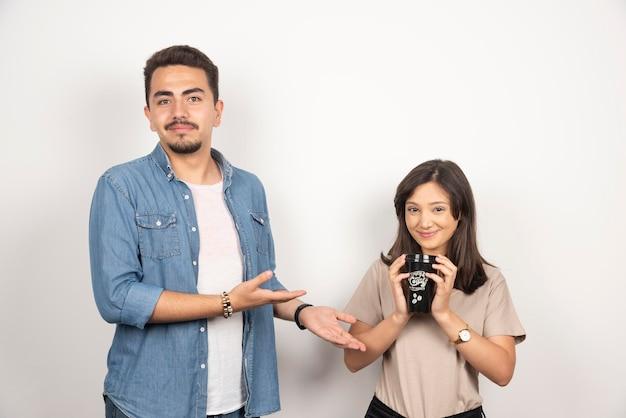 Młody człowiek pokazuje dziewczynę z filiżanką kawy.