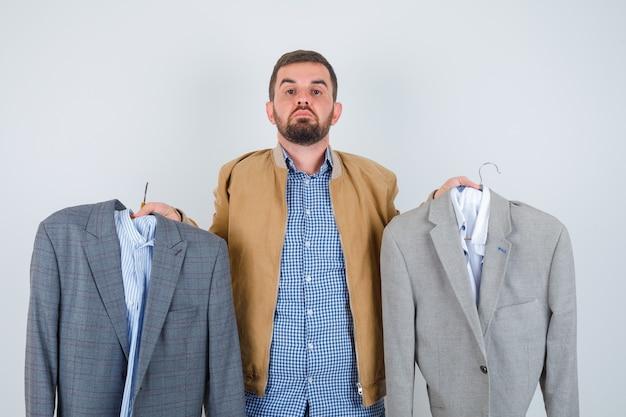 Młody człowiek pokazuje garnitury w kurtkę, koszulę i tęsknie patrząc, widok z przodu.