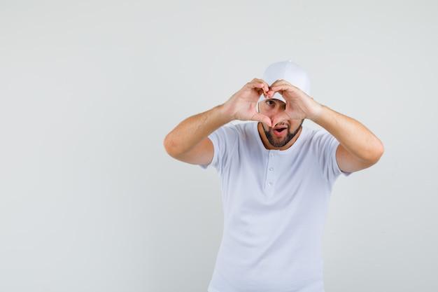 Młody człowiek pokazuje gest miłości w białej koszulce, czapce i patrząc wesoło. przedni widok. miejsce na tekst
