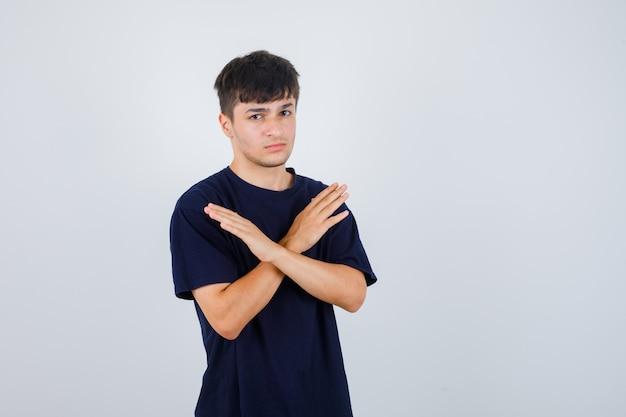 Młody człowiek pokazuje gest odmowy w czarnej koszulce i wygląda poważnie. przedni widok.