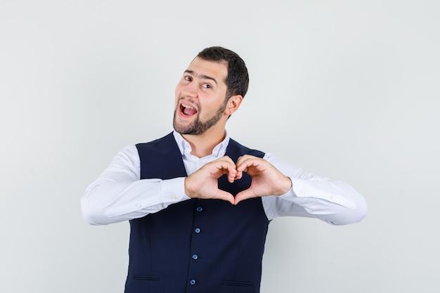Młody człowiek pokazuje gest serca w koszuli i kamizelce i wygląda wesoło