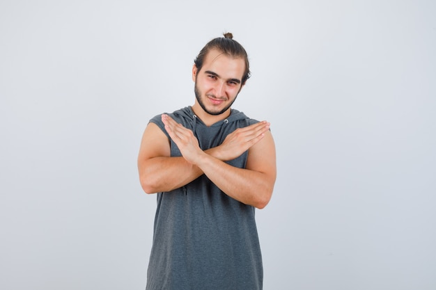 Młody człowiek pokazuje gest stop w bluza z kapturem i przystojny, widok z przodu.