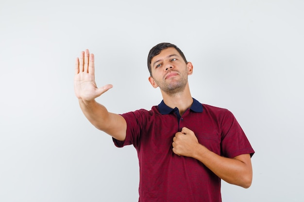 Młody człowiek pokazuje gest stop z pięścią na klatce piersiowej w koszulce i uprzejmy. przedni widok.