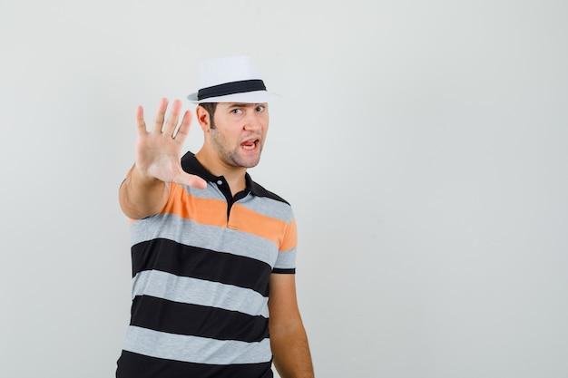 Młody człowiek pokazuje gest stopu w pasiastej koszulce, kapeluszu i patrząc niespokojnie. przedni widok. miejsce na tekst