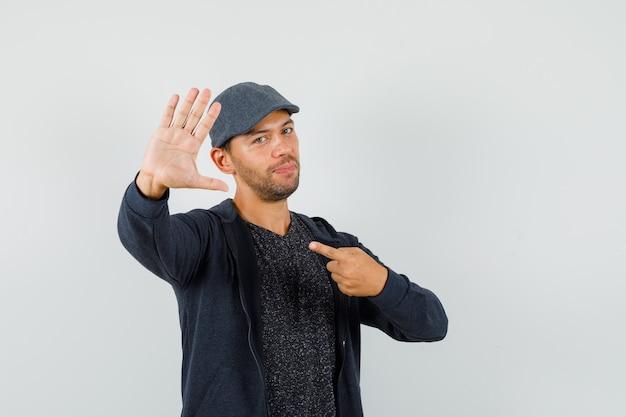 Młody człowiek pokazuje gest stopu, wskazując na siebie w t-shirt, kurtkę, czapkę