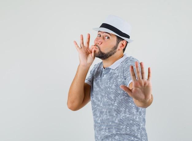 Młody człowiek pokazuje gest stopu z zamkniętymi ustami jako zamek błyskawiczny w koszulce, kapeluszu i zamyślonym spojrzeniu. przedni widok.