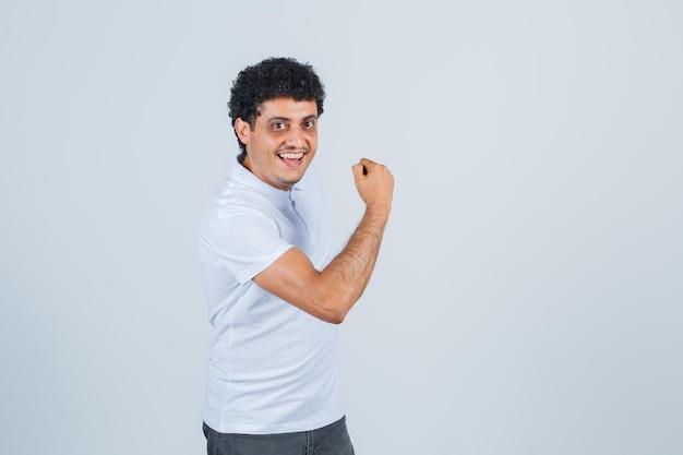 Młody człowiek pokazuje gest władzy w białej koszulce i dżinsach i wygląda na szczęśliwego. przedni widok.