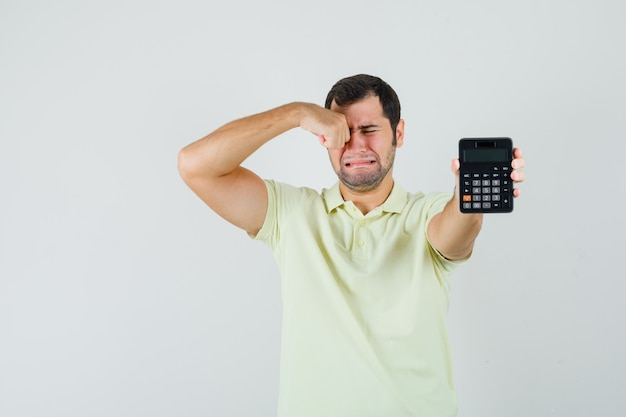 Młody człowiek pokazuje kalkulator płacząc w t-shirt, widok z przodu.