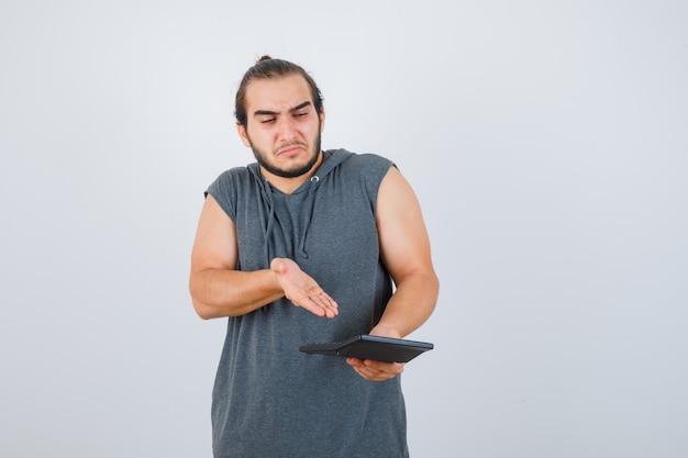 Młody człowiek pokazuje kalkulator w bluzie z kapturem i wygląda ponuro, widok z przodu.