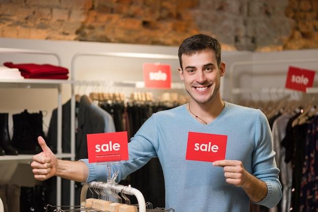Młody człowiek pokazuje kciuk i przytrzymaj czerwony znak ze słowami sprzedaży