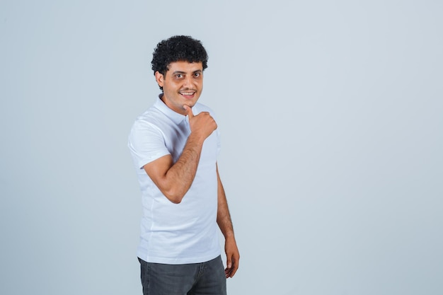Młody człowiek pokazuje kciuk w biały t-shirt i dżinsy i wygląda na szczęśliwego, widok z przodu.