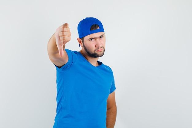 Młody człowiek pokazuje kciuk w dół w niebieskiej koszulce i czapce i wygląda ponuro