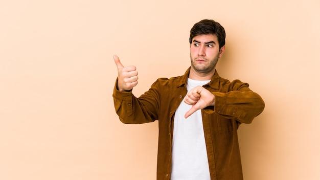 Młody człowiek pokazuje kciuki w górę i w dół, trudno wybrać koncepcję