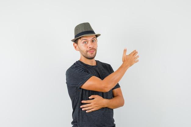 Młody człowiek pokazuje kierunek w t-shirt, kapelusz i szuka pomocnego.