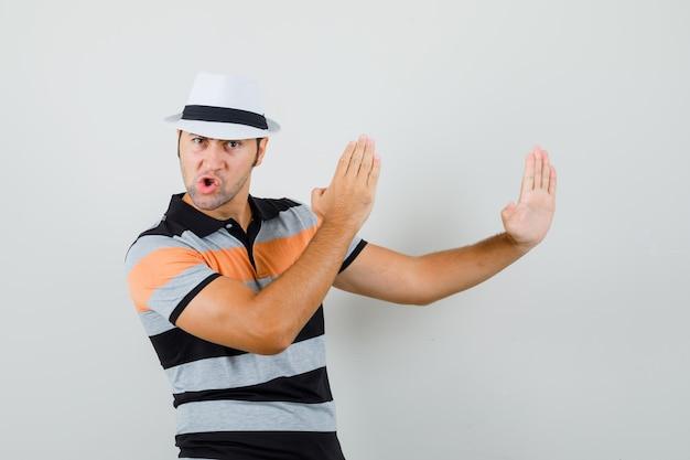 Młody człowiek pokazuje kotlet karate w pasiastej koszulce, kapeluszu i patrząc elastyczny, widok z przodu.