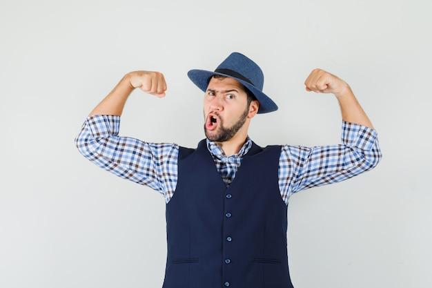Młody człowiek pokazuje mięśnie ramion w koszuli, kamizelce, kapeluszu i wygląda potężnie.