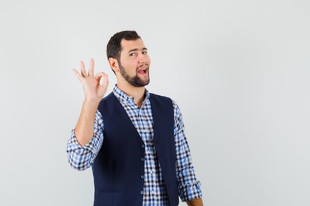 Młody człowiek pokazuje ok gest w koszuli, kamizelce i wygląda pewnie.