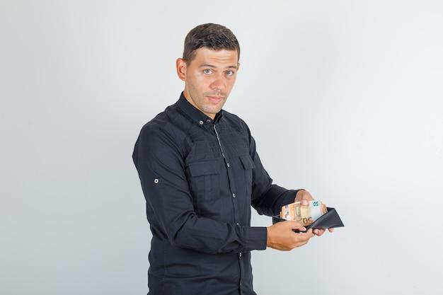 Młody człowiek pokazuje pieniądze w portfelu w czarnej koszuli