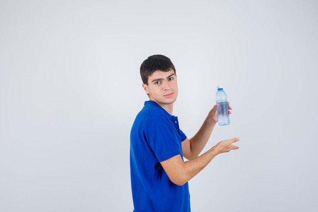 Młody człowiek pokazuje plastikową butelkę w t-shirt i wygląda pewnie