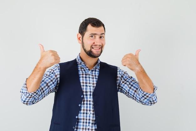 Młody człowiek pokazuje podwójne kciuki w koszuli, kamizelce i wygląda na szczęśliwego