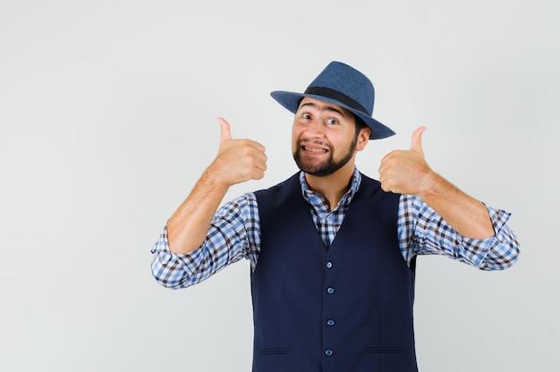 Młody człowiek pokazuje podwójne kciuki w koszuli, kamizelce, kapeluszu i wygląda wesoło.