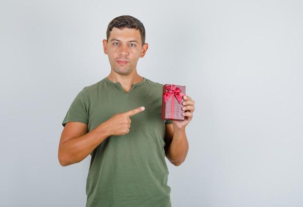 Młody człowiek pokazuje pudełko z palcem w widoku z przodu zielony t-shirt armii.