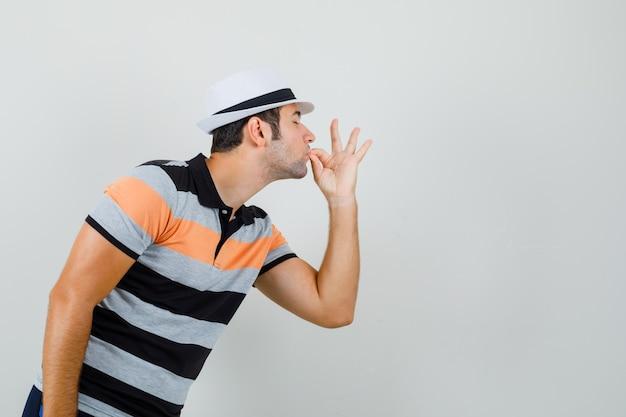 Młody człowiek pokazuje pyszny gest w pasiastej koszulce, kapeluszu i patrząc zadowolony, widok z przodu.