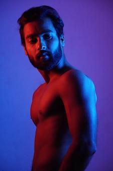 Młody człowiek pokazuje swoją fizykę ze słuchawkami w świetle neonu